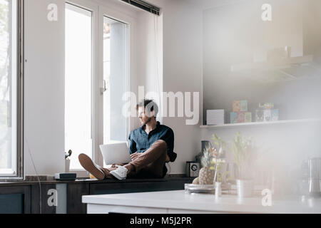 Young man with laptop sitting on window sill in a loft looking out of the window - Stock Photo