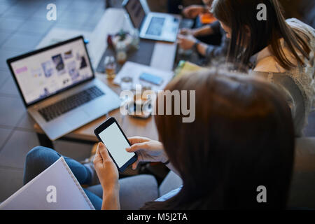 Young woman in cafe using smartphone with friends with laptop in background - Stock Photo