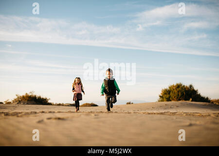 Two children running on the beach in winter - Stock Photo