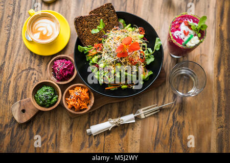 Decorated colorful salad on wooden plate with coffee, water and smoothie on the side - Stock Photo