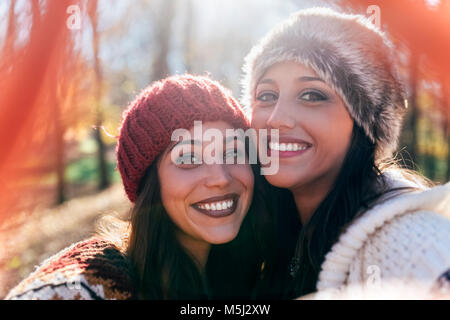 Two pretty women making a selfie in an autumnal forest - Stock Photo