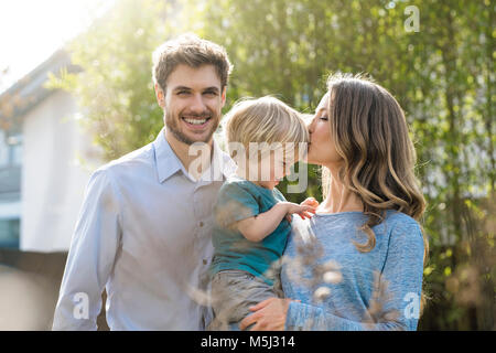 Happy family in garden in front of bamboo plants with mother kissing son - Stock Photo