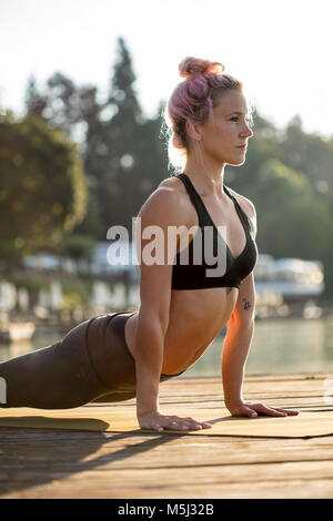 Woman practicing yoga on jetty at a lake Stock Photo