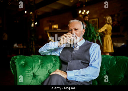 Portrait of elegant senior man sitting on couch in a bar drinking from tumbler - Stock Photo