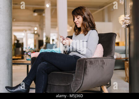 Woman sitting in armchair knitting - Stock Photo