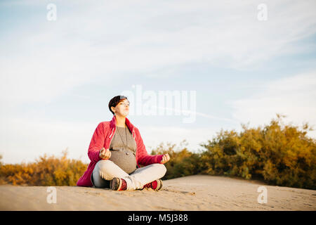 Pregnant woman practicing yoga on the beach in winter - Stock Photo
