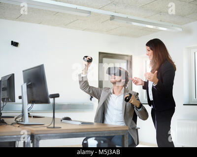 Woman with man wearing VR glasses in office - Stock Photo