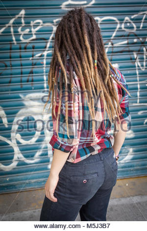 Caucasian woman with dreadlocks looking over shoulder - Stock Photo