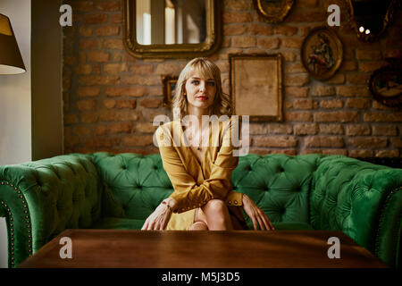 Portrait of elegant woman sitting on a couch - Stock Photo