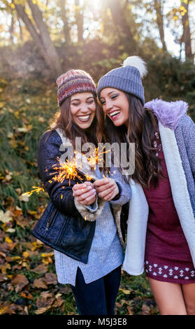 Two gorgeous women having fun with sparklers in an autumnal forest - Stock Photo