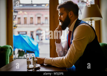 Pensive fashionable young man sitting in a cafe - Stock Photo
