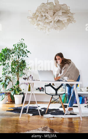 Smiling young woman at home using laptop on desk - Stock Photo