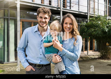 Portrait of smiling parents with son in front of their home - Stock Photo
