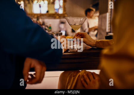 Close-up of elegant couple having a drink at the counter in a bar - Stock Photo