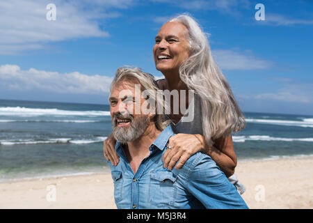 Handsome senior couple having fun at the beach - Stock Photo