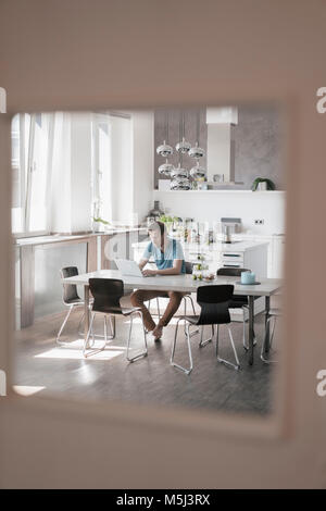 Man sitting at table in the kitchen working on laptop - Stock Photo