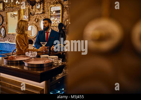 Elegant couple having a drink in a bar - Stock Photo