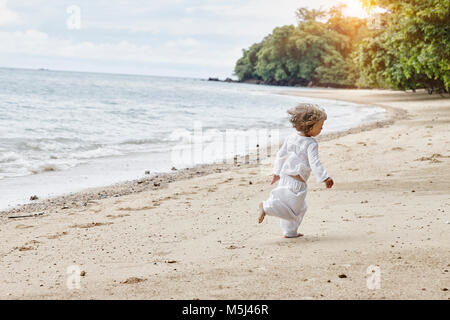 Thailand, Ko Yao Noi, little girl running on the beach - Stock Photo