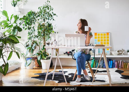 Young woman at home at desk looking sideways - Stock Photo
