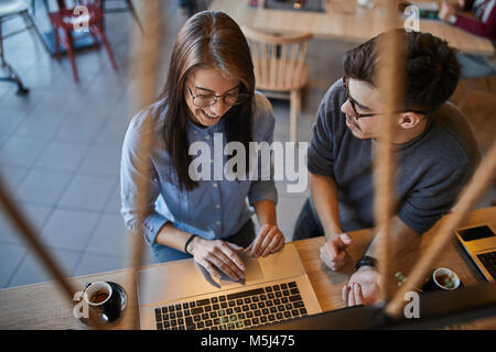 Young man looking at smiling woman in a cafe with laptop - Stock Photo