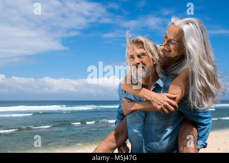 Handsome senior couple having fun at the beach - Stock Photo