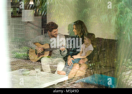 Happy parents and daughter playing guitar on sofa at home - Stock Photo