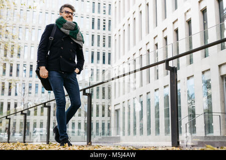 Content businessman walking in the city in autumn - Stock Photo