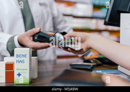 Close-up of customer paying cashless in a pharmacy - Stock Photo