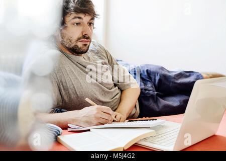 Portrait of student lying on bed with laptop and book learning - Stock Photo