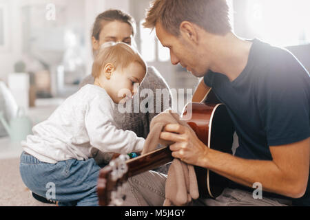 Little girl examining father's guitar at home - Stock Photo