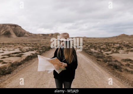 Woman with map standing on dirt road in barren landscape - Stock Photo