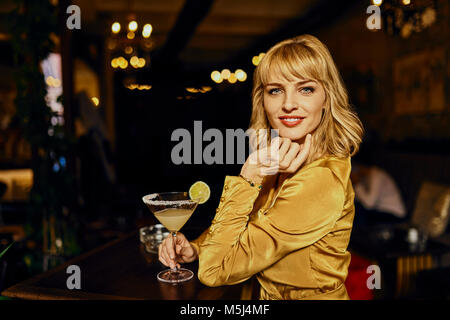 Portrait of elegant woman with cocktail in a bar - Stock Photo