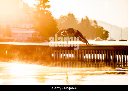 Woman practicing yoga on jetty at a lake - Stock Photo