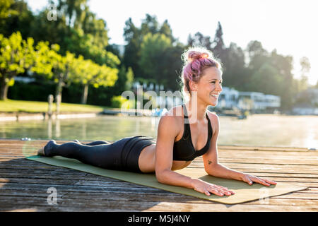 Smiling woman practicing yoga on jetty at a lake - Stock Photo