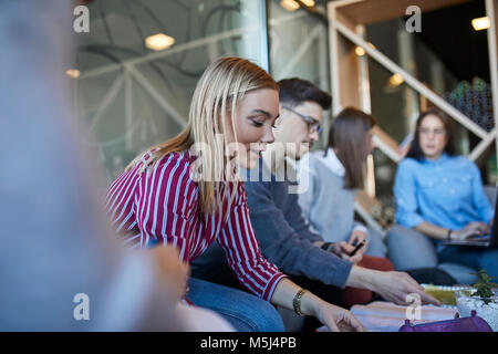 Group of friends sitting together in a cafe discussing documents - Stock Photo
