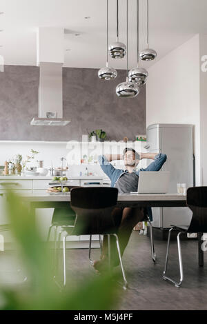 Young man relaxing at table in the kitchen - Stock Photo