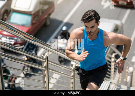 Man in blue fitness shirt running upstairs in city - Stock Photo