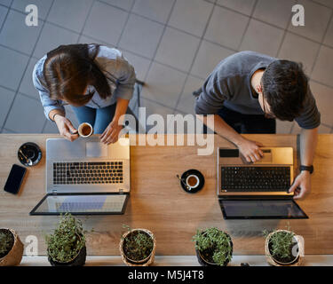 Top view of young woman and man in a cafe using laptops - Stock Photo