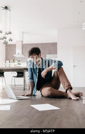 Young man sitting on the floor in a loft using laptop - Stock Photo