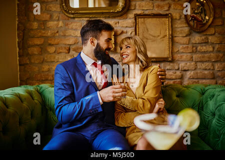 Happy elegant couple sitting on couch embracing - Stock Photo