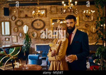 Portrait of elegant couple with drinks in a bar - Stock Photo