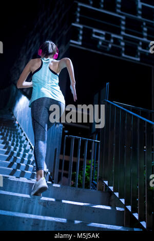 Young woman with pink headphones running upstairs in modern urban setting at night - Stock Photo