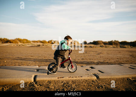 Boy running with a bike on the beach in winter - Stock Photo