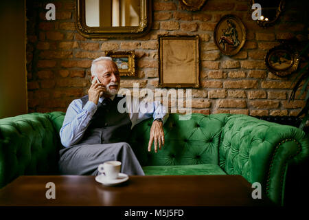 Elegant senior man sitting on couch in a cafe talking on cell phone - Stock Photo