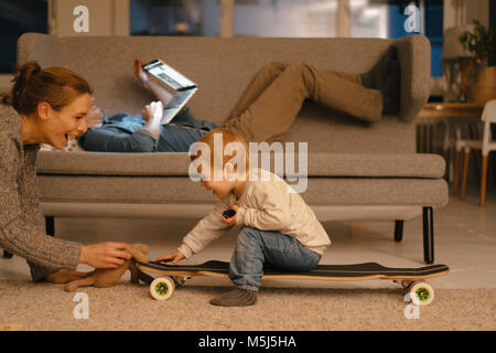 Mother playig with daughter with father using laptop in background - Stock Photo
