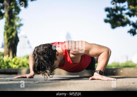 Athlete doing push-ups in urban park - Stock Photo