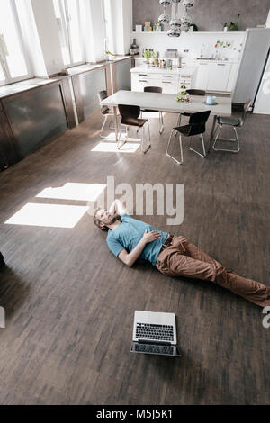 Pensive man lying on the floor in a loft - Stock Photo