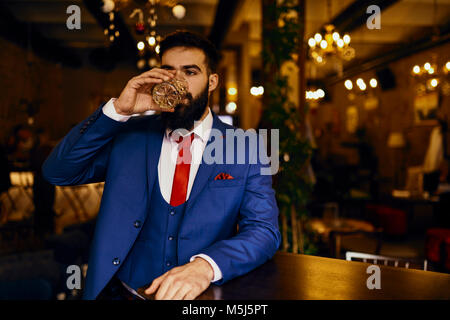 Eegant young man in a bar drinking from tumbler - Stock Photo