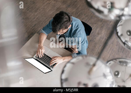 Young man working on laptop, top view - Stock Photo