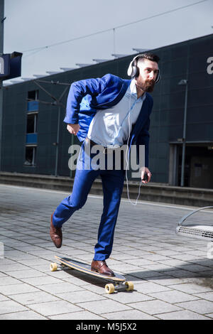 Young man with longboarding at train station, using headphones - Stock Photo